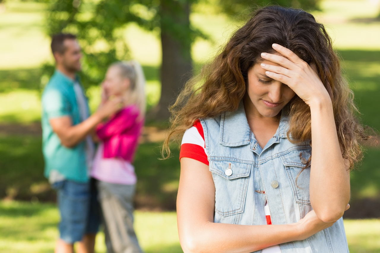 12162146_angry-woman-with-man-and-girlfriend-in-background-at-park